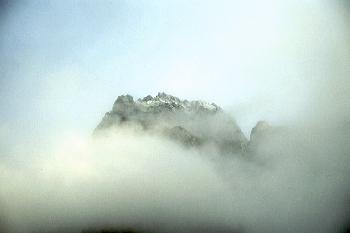 Berggipfel der die Sonne trotz Wolken findet